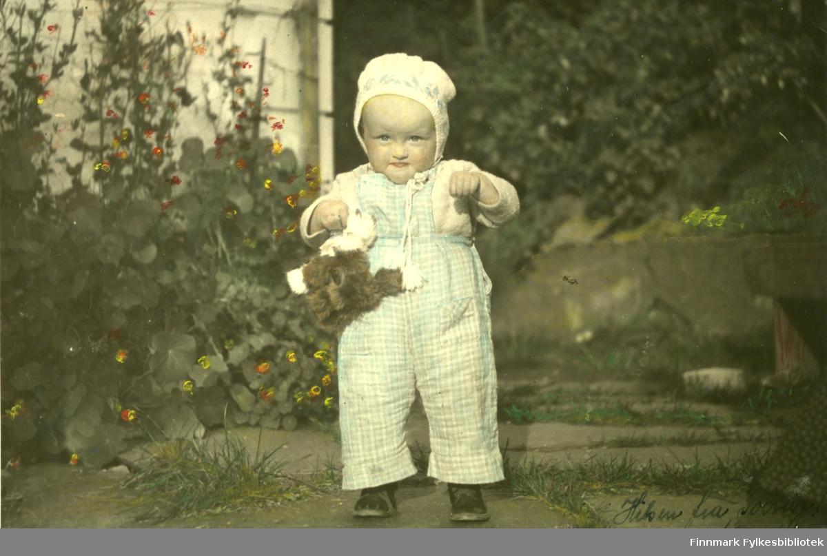 Portrett av Solveig Lunde i Bergen som barn. Hun er barnebarn til August Magnus Jacobsen, og oldebarn til smedmester i Vardø Ole Sigfrid og hustru Anna Christine Vibe Jacobsen. På bildet er hun ute i en hage. I hånden holder hun en leketøyskatt. Hun er kledt i lyse klær og på hodet har hun en hvit lue med snøring