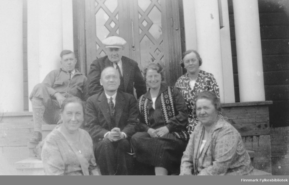 Fotografi av tre menn og fire kvinner som sitter på en trapp. Mannen i midten er sannsynligvis fotografen Olaf Adolf Jacobsen fra Vardø. Han hadde atelier både i Vardø og Kirkenes. Bak personene er det en bred dør med utskjæringer som pynt. På begge sider av inngangspartiet står det hvite søyler