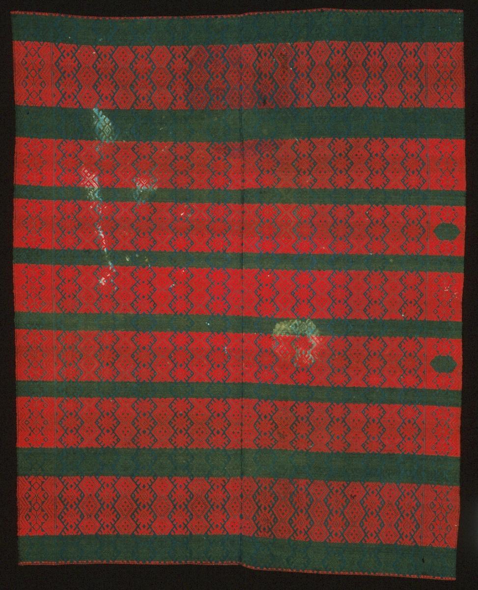 """Randigt täcke vävt i opphämta med röda och gröna mönsterbårder på indigoblå botten. Täcket kan också ha använts som bordtäcke/duk. De röda bårderna är ca 150 mm breda, de gröna är ca 50 mm. Mönsterformer av snedställda rutor och snedställda rutor med taggar. Mönsterbårder på längden, färgränder på bredden. Stjärnmönstrad bård längs långsidorna. Intill en kortsida avviker två snedrutor i de röda inslagspartierna som istället gjorts gröna. Täcket är avslutat i kortsidorna med en smal röd mönsterrand, fållad kant. Stadkanter i långsidorna. Inslagsgarnet ligger löst en liten bit utanför de yttersta varptrådarna i långsidorna. Täcket är ihopsytt på mitten av två delar á 650 mm bredd.Varp i blått 1-trådigt z-spunnet lingarn, 16 trådar/cm.Botteninslag samma som varpgarnet, 10 trådar/cm.Mönsterinslag i rött och grönt 2-trådigt s-tvinnat ullgarn, mycket kraftig tvinning/snodd.Märkt på baksidan med påsydd tyglapp med texten: """"N° 153 a. Torna"""".Fläckigt."""