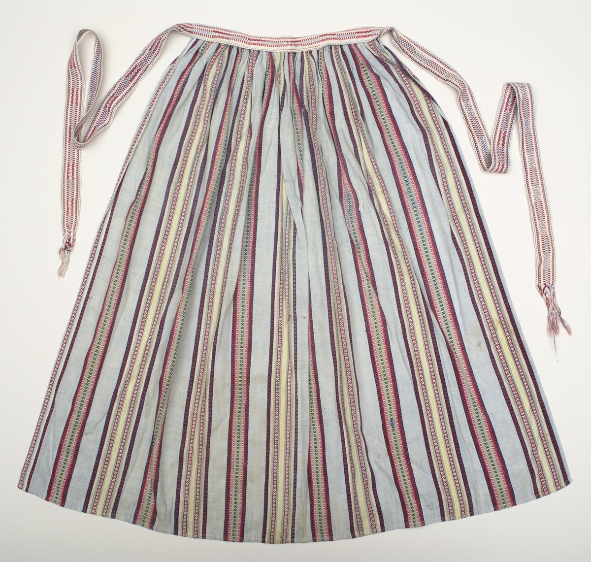 Bomullsförkläde vävt i rosengång i ljusblått, rött, rosa, gult, vitt och mörkblått. Mönsterrapporten 165 mm bred. Bredd nertill 955 mm, med fåll 8 mm, sidfåll 3 mm. Förklädet rynkat mot linningen som är av samma tyg som förklädet, framtill är ett band, 27 mm brett, påsytt. Bandet är mönsterplockat i rött, vitt och två nyanser blått. Bandet fortsätter som knytband 880 mm med flätad avslutning upp till 100 mm.  Äldre märkning KK 14.