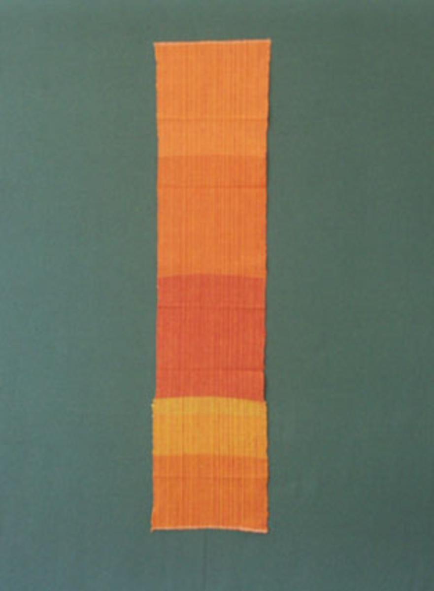 Prov till cottolintyg enligt tidigare inventering, i olika orange-röda nyanser med cottolin i varp och cottolin och lingarn i inslag.