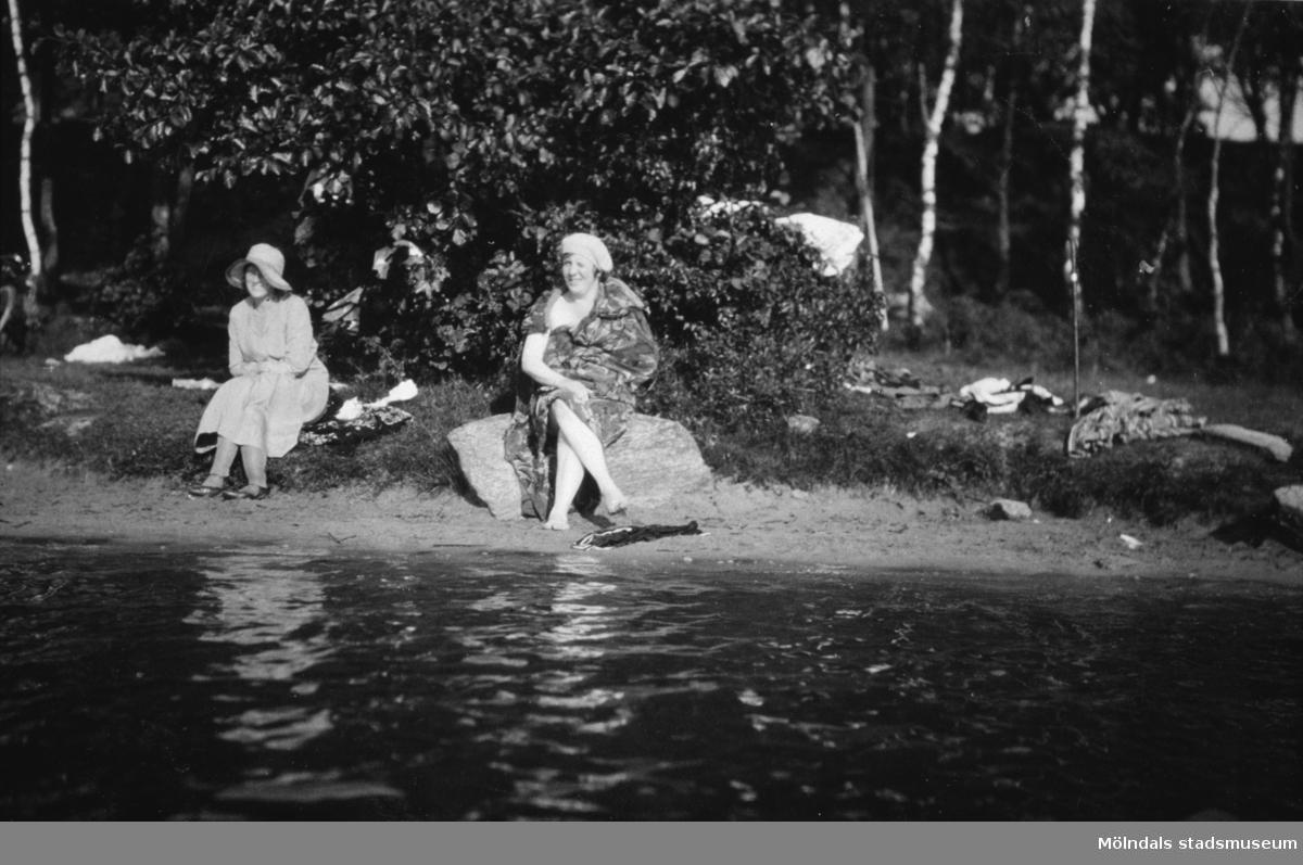 Fru Ester Alberts (gift med Karl Alberts) sitter på stenen vid Tulebosjön. Mattor tvättades på stenen då vattnet var högre. Okänd till vänster.