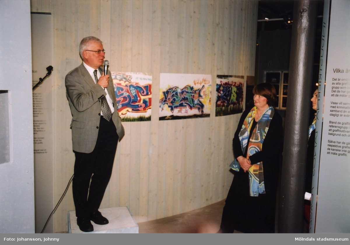 """Man håller tal i utställningen """"Alltså finns jag"""" på Mölndals museum, år 2003. Till höger ses museichef Mari-Louise Olsson.  Utställningen """"Alltså finns jag"""" ...en utställning om graffitikultur på Mölndals Museum, Kvarnbygatan 12, Mölndal, pågick från 25 januari till 25 maj 2003.  """"Alltså finns jag"""" var ett samarbete mellan Mölndals museum, Vitlycke museum, Bohusläns museum, Västergötlands museum och Konstkonsulenterna i Västra Götalandsregionen."""