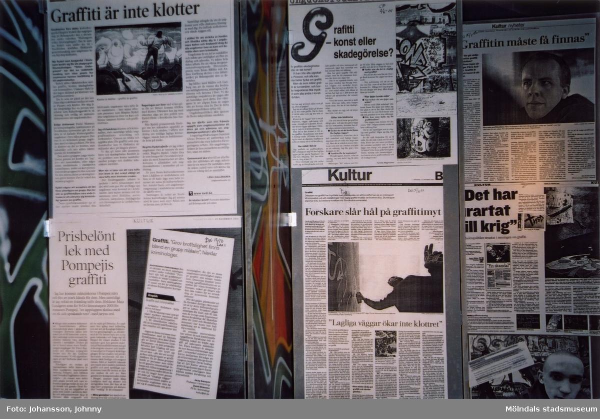 """Fotografi som visar utställningen """"Alltså finns jag"""" på Mölndals museum, år 2003. Tidningsurklipp.  Utställningen """"Alltså finns jag"""" ...en utställning om graffitikultur på Mölndals Museum, Kvarnbygatan 12, Mölndal, pågick från 25 januari till 25 maj 2003.  """"Alltså finns jag"""" var ett samarbete mellan Mölndals museum, Vitlycke museum, Bohusläns museum, Västergötlands museum och Konstkonsulenterna i Västra Götalandsregionen."""