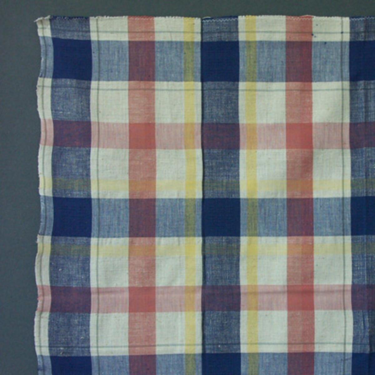 Rutigt duktyg i tuskaft med partier av stramaljbindning i de mörkblå rutorna. Tyget har bomullsgarn i varp och bomull och cottolin i inslag och mönsterpartier i rosa, blå, gul och grå färg.