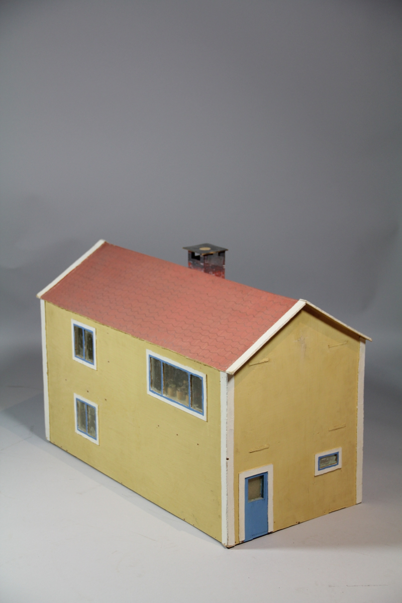 Dukkehus i tre, i to etasjer. Åpent på en side. Totalt fem rom med trapp i midten. Alle rom er tapetsert med papir. Noe veggfast innredning på bad og kjøkken. Rødt tak med pipe. Vindu i taket, bak og i sidene. Gulmalt utenpå med blå dører. Utført i finerplater.