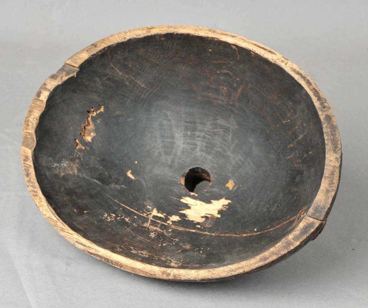 Oval trakt, uthola av tre med tut på undersida. Trakta er sprukket, men seinare reparert med to jernspiker.