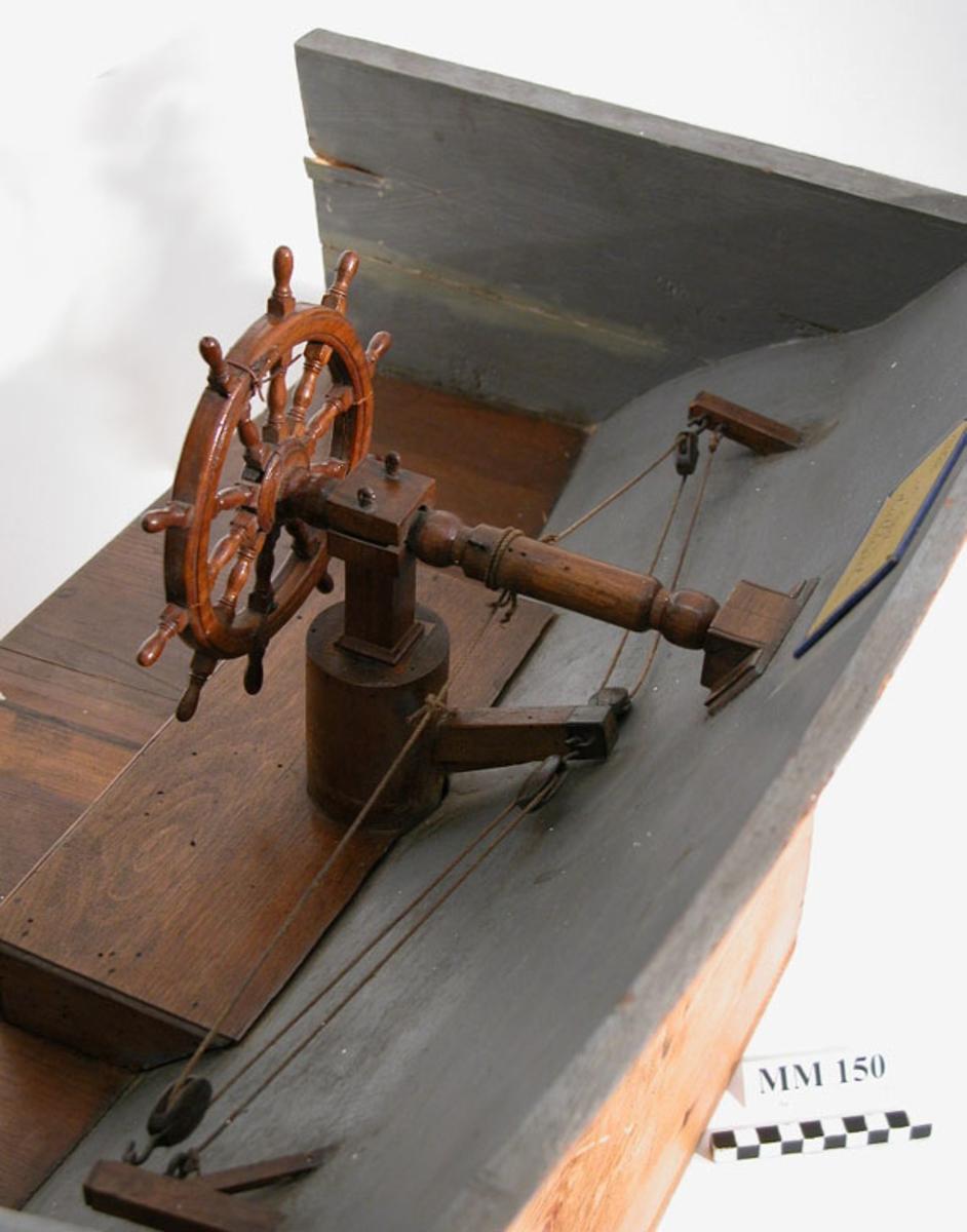 Drillhjul, beslaget. Modell av trä, fernissad. Modellen fastsatt till akterskeppet av ett fartyg, gråmålat.