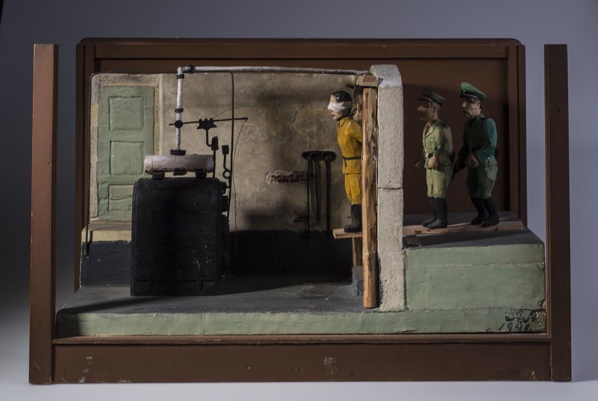 Modell som viser hvordan hengignen av 17 krigsfanger foregikk i fyrrommet på Vollan fengsel. To tyske soldater stod på en løs planke som stakk utover et høyt trinn. Fangen ble plassert ytterst på kanten av planken med løkke rundt halsen. Når soldatene hoppet av, falt planken ned, og fangen mistet fotfestet og ble hengt.