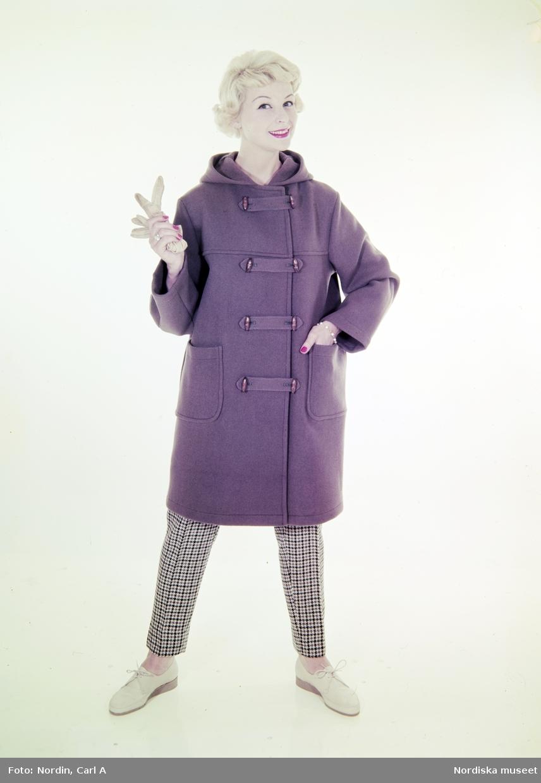 Modell i brun duffel, rutiga byxor och handskar i handen.