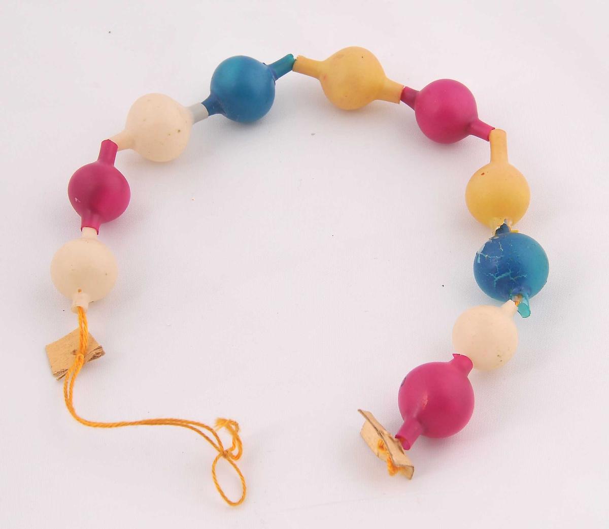 9 (inkl. ei skada) matte einsfarga kuler, tre ulike fargar, som er tredd inn på ein bomullstråd så det dannar eit kjede.