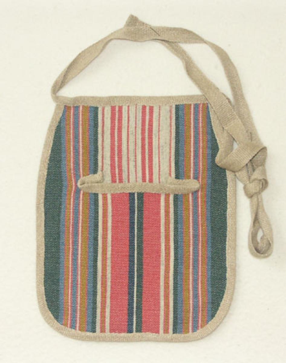 """Kjolsäck till Sunnerbodräkt sydd i halvylletyg vävt i oliksidig korskypert.  Kjolsäcken är kantad med ett linneband som också använts till handtag/rem och baksidan består av ett kraftigare oblekt linnetyg.Kjolsäcken togs fram omkring 1980 efter en gammal förlaga från Nöttja socken som finns på Nordiska museet. På baksidan är det märkt """"Nöttja 47822"""" (Nordiska muséets märkning) och en etikett från Kronobergs hemslöjd Växjö."""