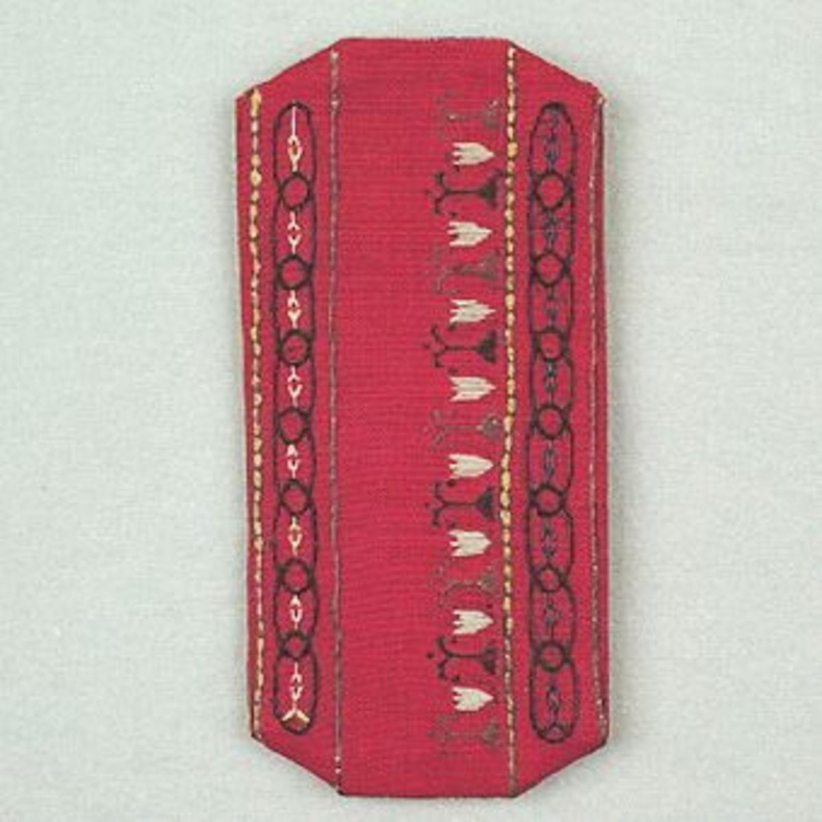 """Ett glasögonfodral i rött linne, Ölandslinne, med broderi i brunt, blått, grönt och vitt. Brodergarn lingarn och knyppeltråd. Etikett med prisuppgift  och texten """"Sylön ? x dd"""" finns fastsydd på  fodralet. Färdigt fodral 12 kr och material 4,50 kronor.Glasögonfodralet har SHR:s pappersetikett från Kronobergs Läns Hemslöjdsförening Växjö, med påskrivet nummer: """"1422"""", fästad vid sig."""