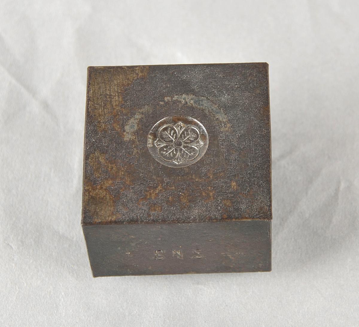 Stålstanse til sylvknapp med blomemotiv, fire kronblad. Kvadratisk blokk med sirkelforma fot. Stempel i eine sida.