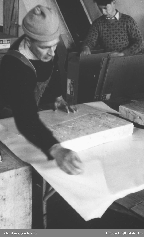 Arbeid på 'frysa' på filetfabrikken i Øksfjord, 1953. Egil Krudtå pakker fiskefileter. Jon Berntzen i bakgrunnen