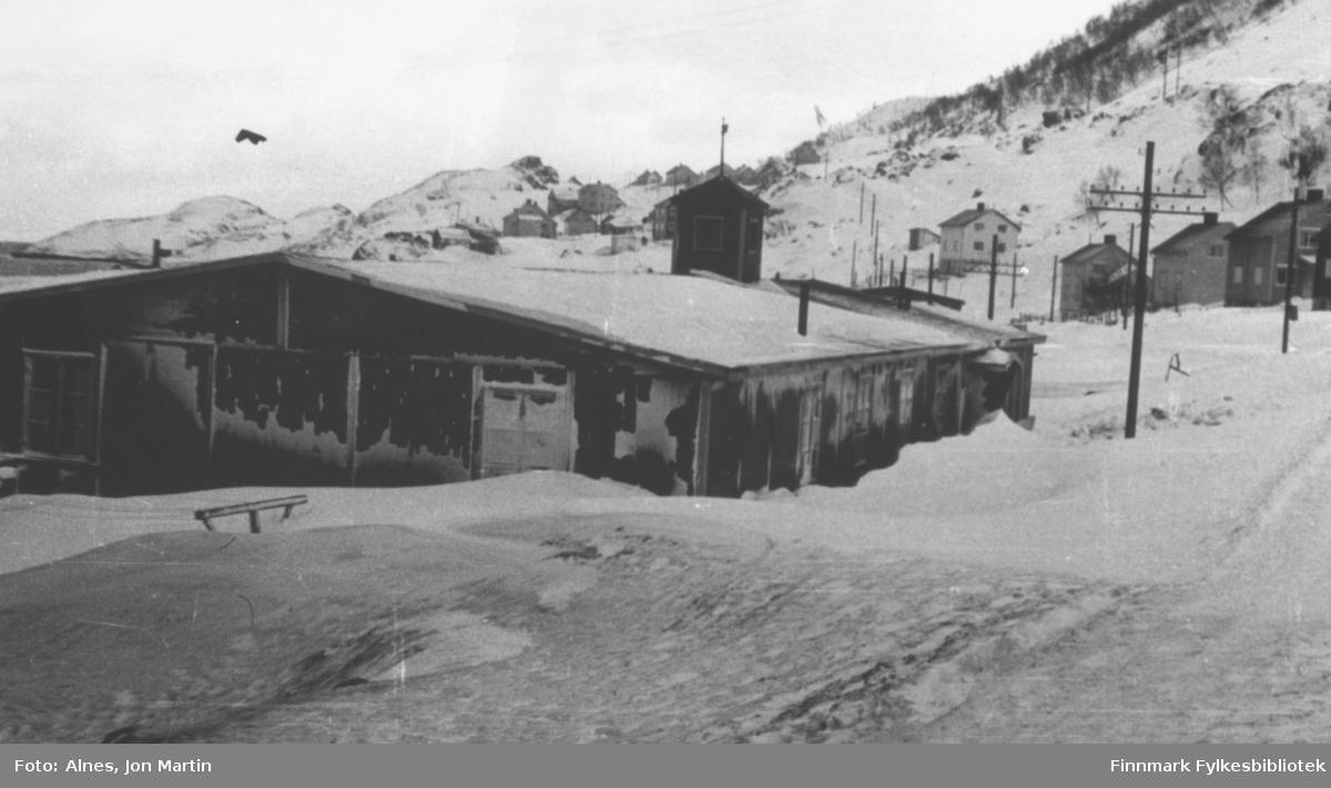 Øksfjord fotografert utover mot Hankenbakken i 1953. I forgrunnen den gamle kirkebrakka, som også ble brukt som skolehus etter krigen. Brakka sto mellom der Coop Øksfjord og Øksfjord bilservice er i dag (2006)