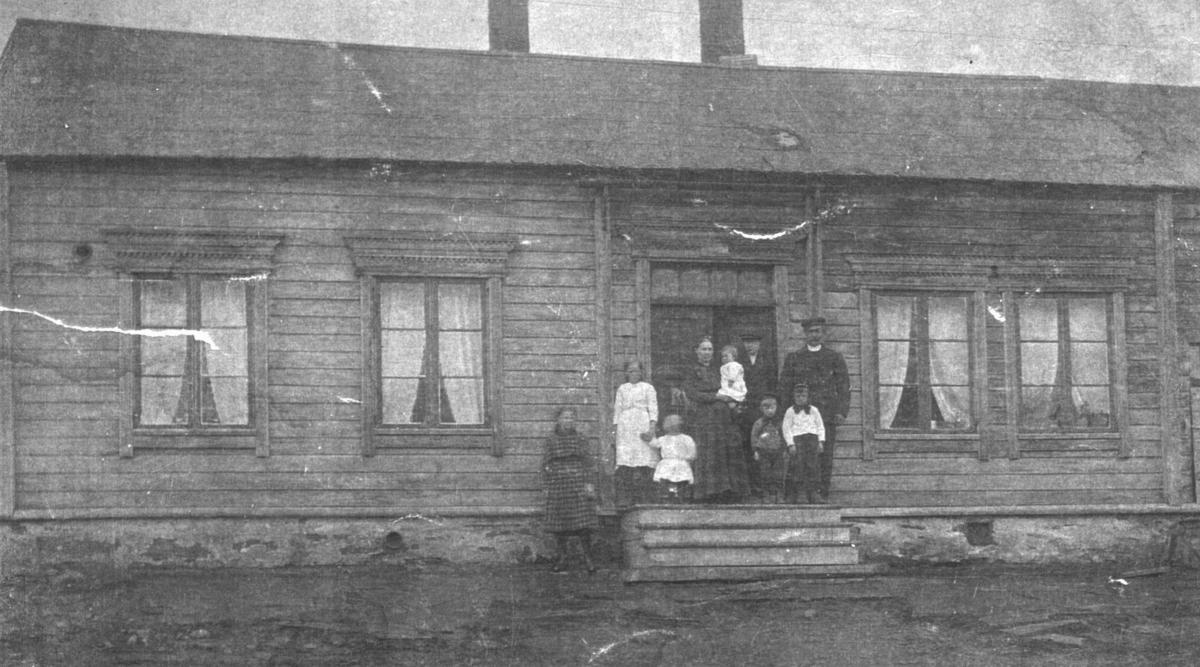 Tradisjonelt bolighus i Hvistedalsgate 55. Familie på tre voksne - en kvinne og to menn- og seks barn står på trappa. Huset er bygd av laftet tømmer og har inngangen i midten.