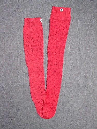 """Ett par röda spetsstickade ullstrumpor i barnstorlek. Motivet kallas """"björklöv"""". Resårstickad kant högst upp på skaftet, därunder en slätstickad bård innan mönstringen tar vid. Foten är slätstickad. Fastsydd vit knapp på sidan på resårkanten. Enl. Ulla Melins inventering:""""Mönster """"Björklöv"""". Användes på 1880-talet till strumpor. Se Gotländsk Sticksöm av Hermanna Stengård sid 38.""""  Sökord: Ull."""