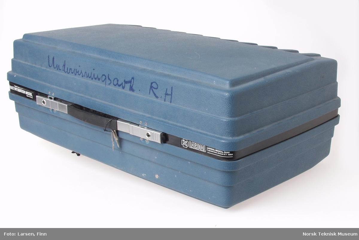 Koffert med hode og lunger til opplæring i livreddende førstehjelp, samt div sprøyter, slanger m.m. Rød lampe i koffert for angivelse av pust.