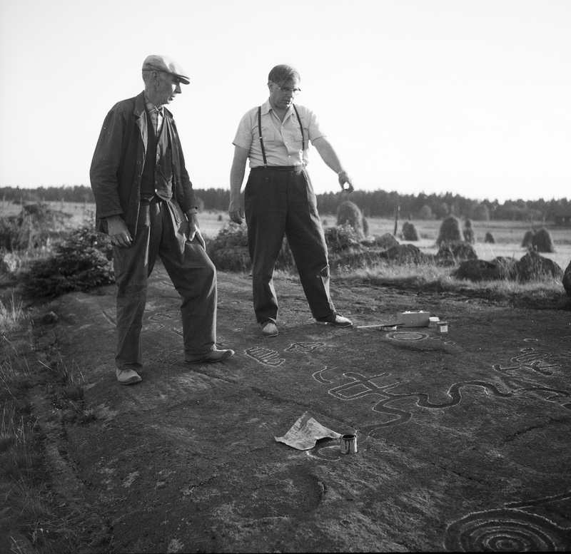 Hällristningar i Evenstorp. Hällristingarna imålas av landsantikvarie Sven-Axel Hallbäck med lantbrukare Aron Andersson som åskådare.