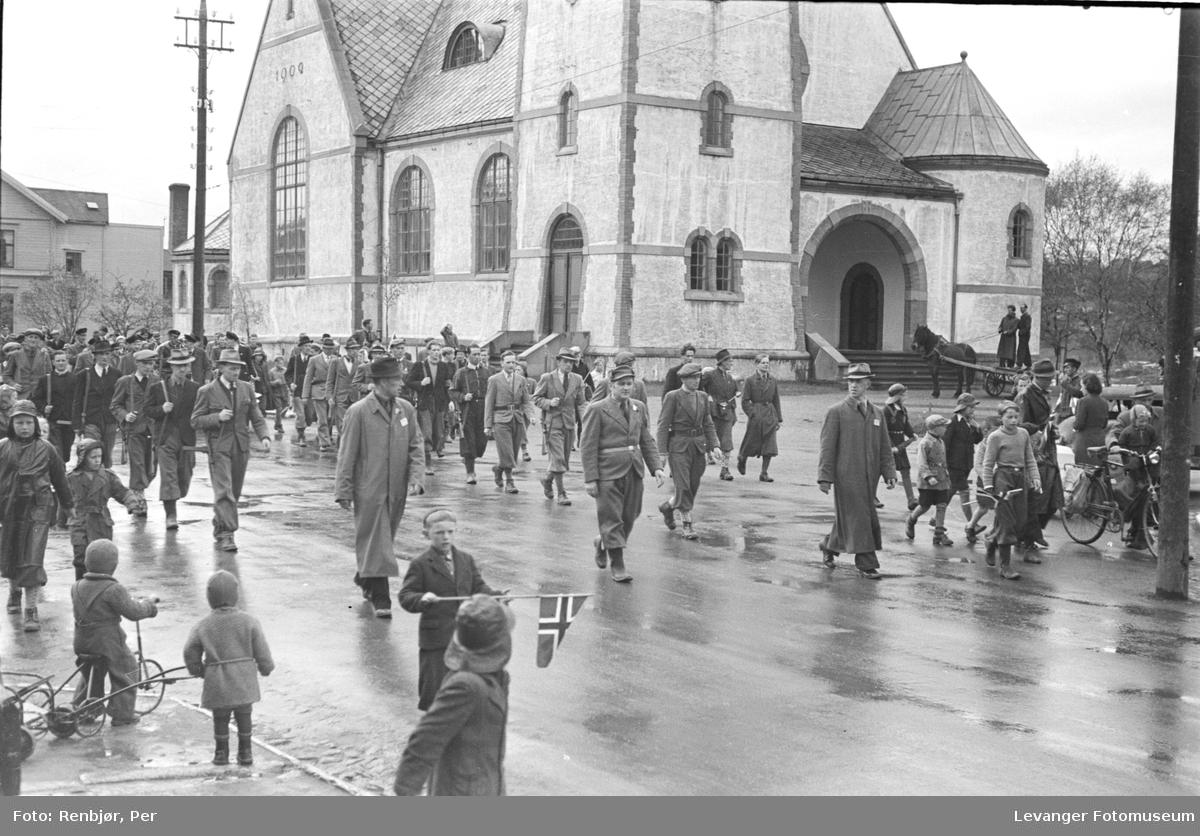 Norske motstandsmenn marsjerer i gatene, de amerikanske fallskjermtroppene lengre bak.
