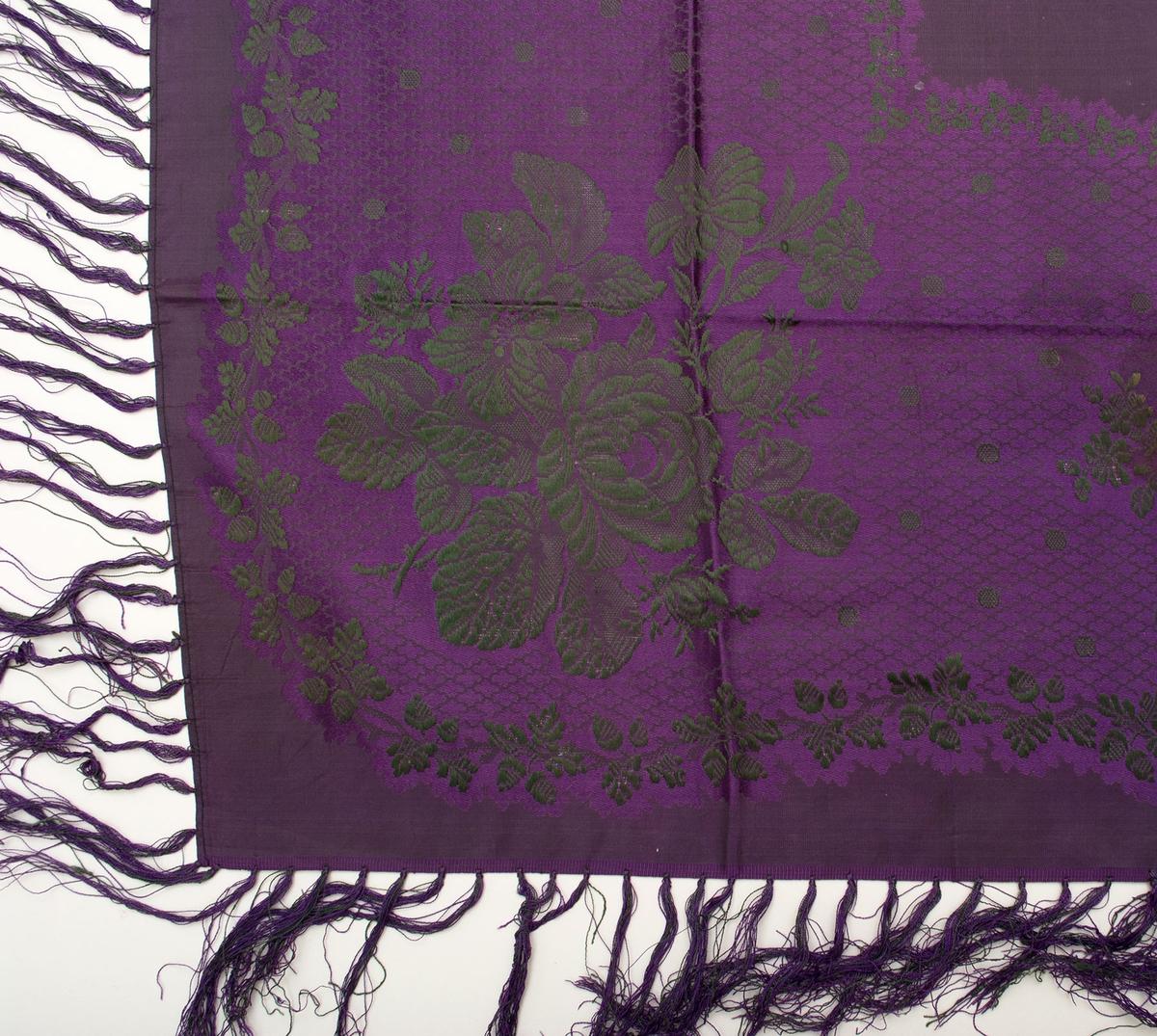 """Blommönstrad sidenschal med frans. Mönstret med rosor, blad, rankor och prickar i grönt på småmönstrad botten i lila löper runt om som en 23 mm bred bård med vågiga kanter. Slät omönstrad yta mitt i; ca 280 x 280 mm, liksom längs kanterna. Stadkant i två sidor, maskinfållad i två sidor. Iknuten 100 mm lång frans längs alla fyra sidor i lila och grönt tvåtrådigt silke, 12 mm mellan varje knut. Varp och botteninslag i lila silkegarn. Inslag i grönt silkegarn. Märkt på baksidan med påsydd tyglapp med texten: """"N° 175 a.  Färs h-d."""". Mått exklusive frans."""