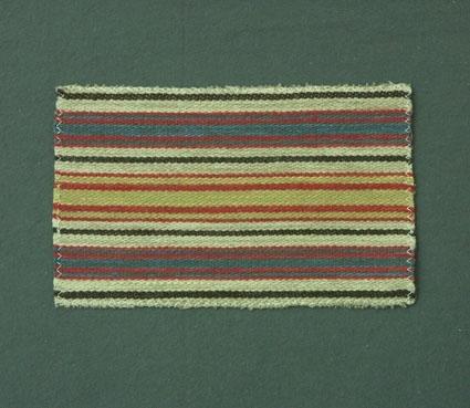 Randigt möbeltygsprov i blått, rött, gult, oblekt och brunt, vävt i korskypert med bomullsgarn i varp och ull- och lingarn i inslag.