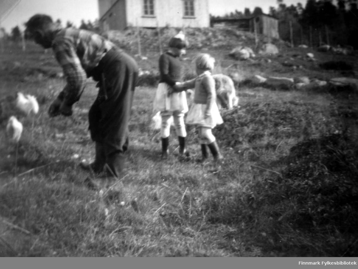 Fotografi av Abiel Randa, Edith og Grethe Stenbakk. De er ute på en eng, nedenfor et hvitt hus. Til høyre for huset ses et trebygning. Det er skog i bakgrunnen. Abiel står bøyd mot to høner. Han er kledt i rutete skjorte og mørke bukser. Jentene er kledt i hvite skjørt og strikkagensere. På bena har de støvler. Edith har en hvit hårsløyfe