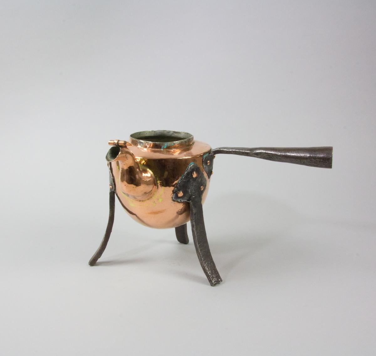 Kaffepanna tillverkad av koppar. Svängd pip med lövformat lock. Förtent insida. Handtag av järn, bockat för en förlängning av trä. Tre svagt svängda ben av järn med hjärtformade fästen nitade mot pannan.