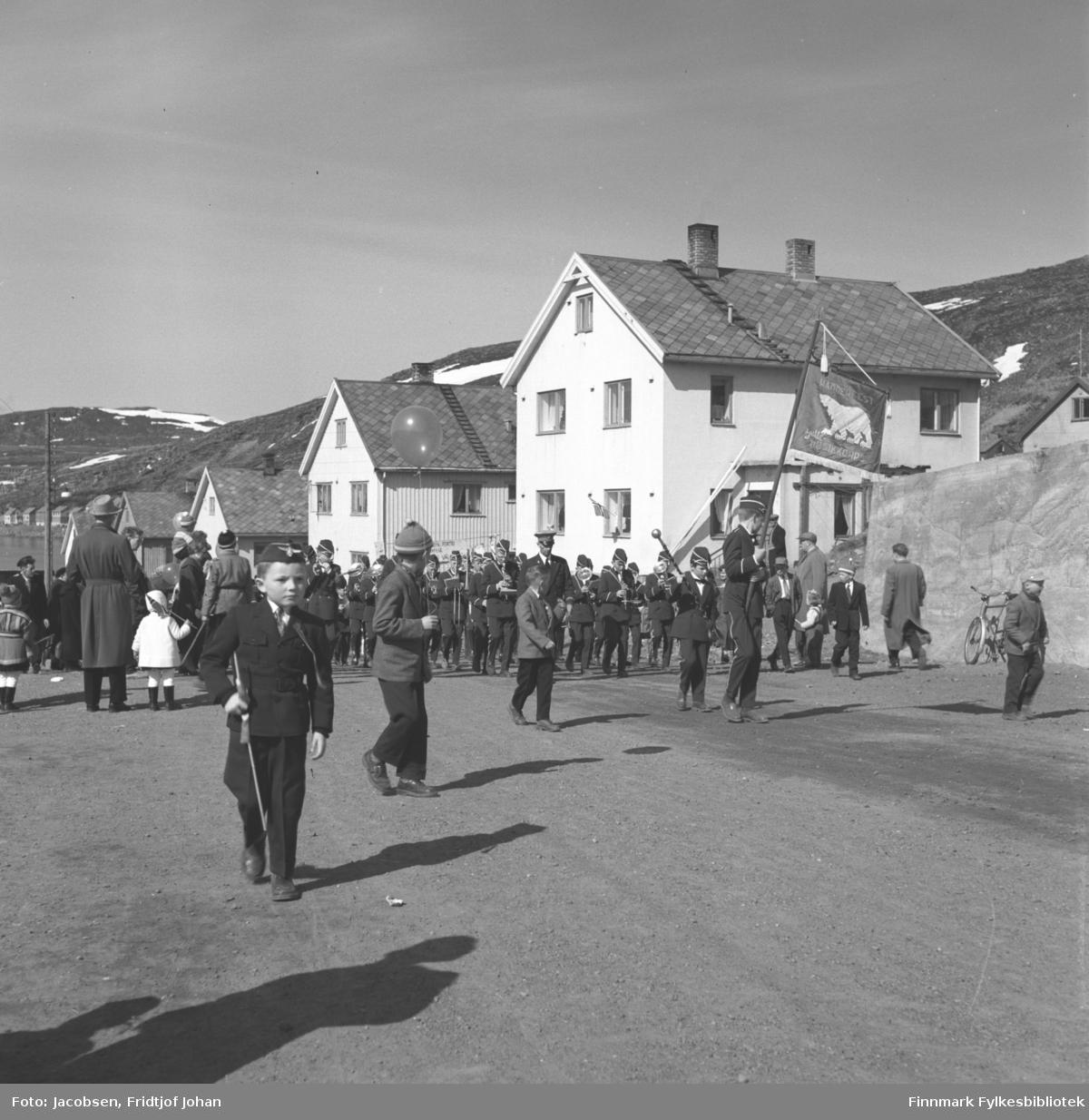 17. mai-feiring i Hammerfest. Bildet viser et musikk-korps og flere festkledt mennesker i Skolebakken. Huset til høyre på bildet tilhørte Alf Paulsen som var dirigent for skolekorpset.
