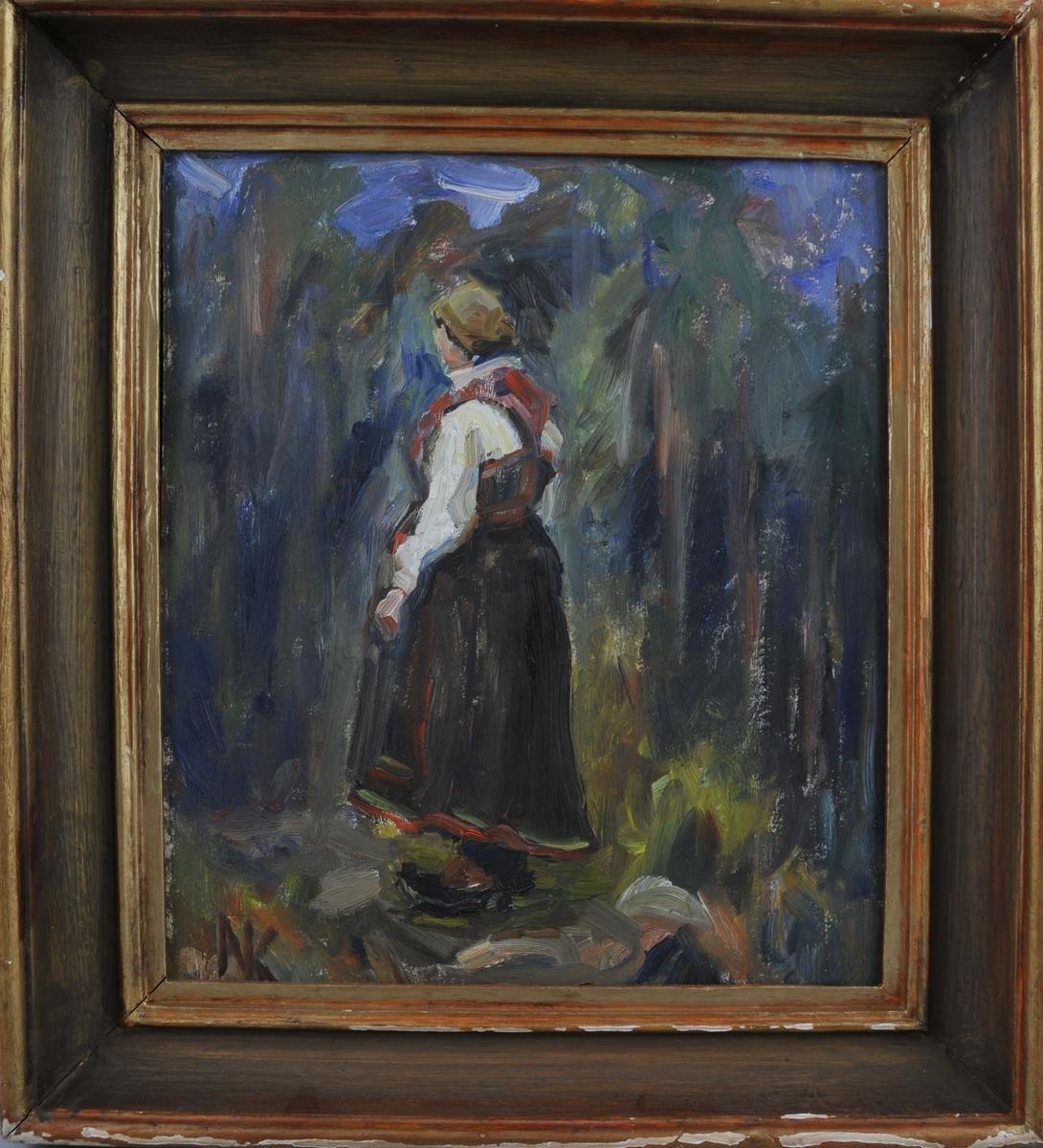 Kvinne i bunad som står i eit skogslandskap, delvis med ryggen mot målaren.