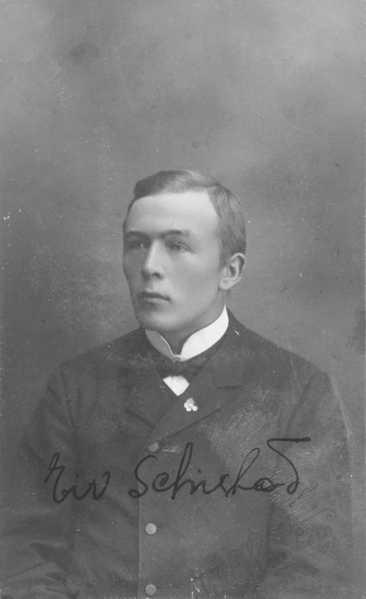 """Portrett i halvfigur av mannsperson. På bildet er det notert Eiv. Schistad. Dette kan være Eivind Bernhard Schistad, født 17.12.1885 i Vadsø. Han er registrert som skolegutt i år 1900, under folketellingen i Vadsø kjøpstad, iflg. Digitalarkivet. Senere er han registrert som """"baker"""" i Kristiania i 1910. I folketellingen for Vadsø år 1900 står det at hans far er Sigvard Schistad; """"Fiskeriopsynsbetjent"""" født 1854 i Vadsø. Hans mor er Hanna Malene Schistad, født 1954 i Vadsø. Brødrene er Halfdan Gustav Olaf Schistad (1884), Ragnvald Johan Schistad (1887), Haakon Birger Schistad (1889) og Magnus Berg Schistad (1891), jfr. Digitalarkivet. Portrettet er tatt av fotograf J.H. Wennberg som virket i Tromsø. Fotograf Wennberg var født i Sverige i 1856 og var registrert med adresse Søndre Kirkegade under folketellingen i 1885."""