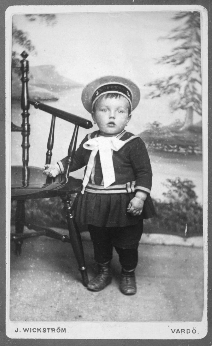 Portrett fra en liten gutt i matrosedrakt, Albert Palo (Ballo). Han står ved en stol foran an malt bakrunn (landskapsmotiv ). På bildet er han ca 3 år gammel. Bildet er samme som bilde nummer 05021-017, men av bedre kvalitet.