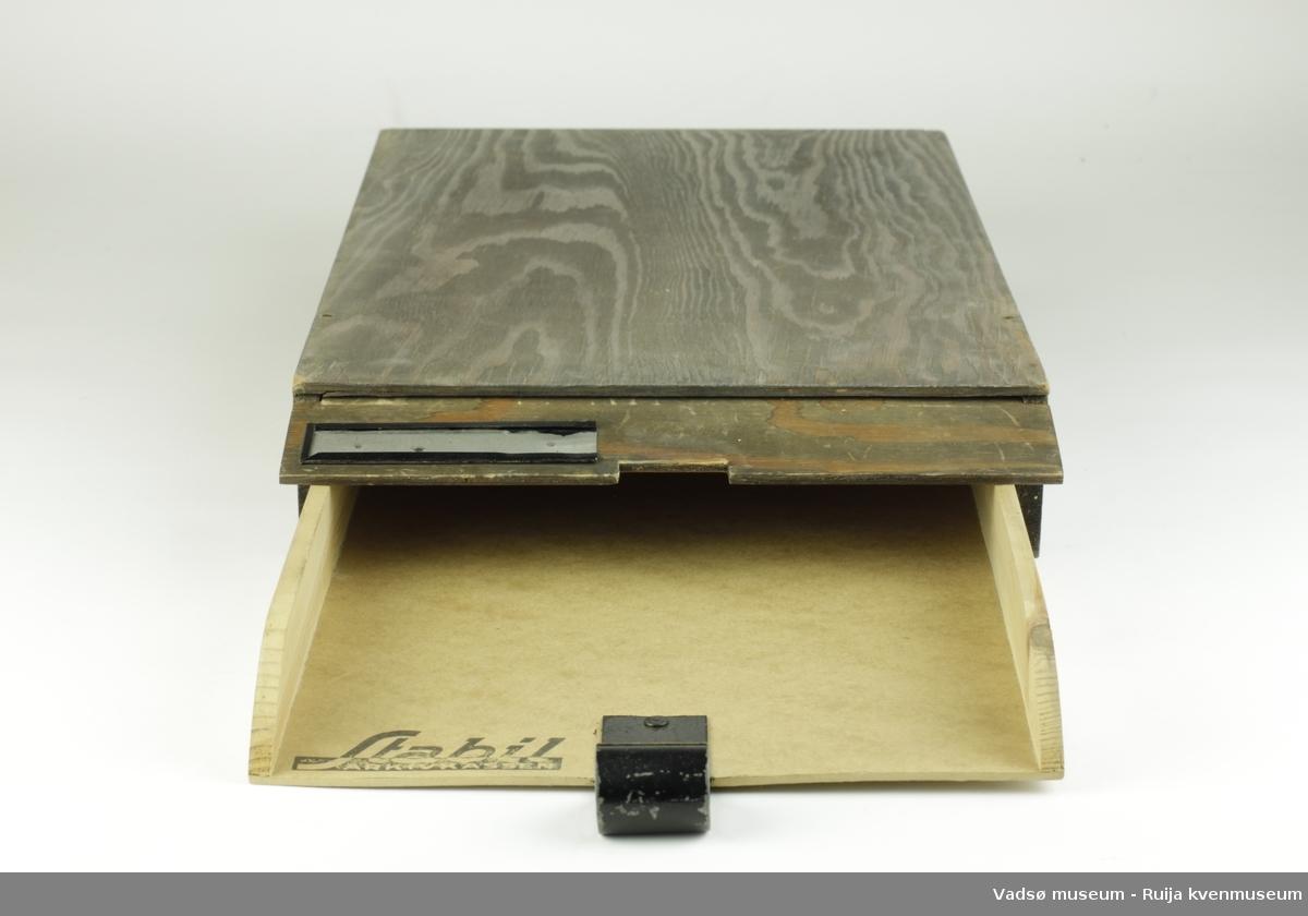 Arkivkasse. Består av ytterkasse og innvendig skuff. Ytterkasse av tre, lakkert med brun matt lakk. Åpen i front, med lokk foran. Skuffen inni består av side-elementer i ubehandlet tre, festet i lett bunnplate av sammenpresset materiale. Skuffen er åpen i front for lett tilgang til dokumenter, og har håndtak i metall som stikker utenfor ytterkassen. Metallbeslag på ytterlokk for merking av kassen.