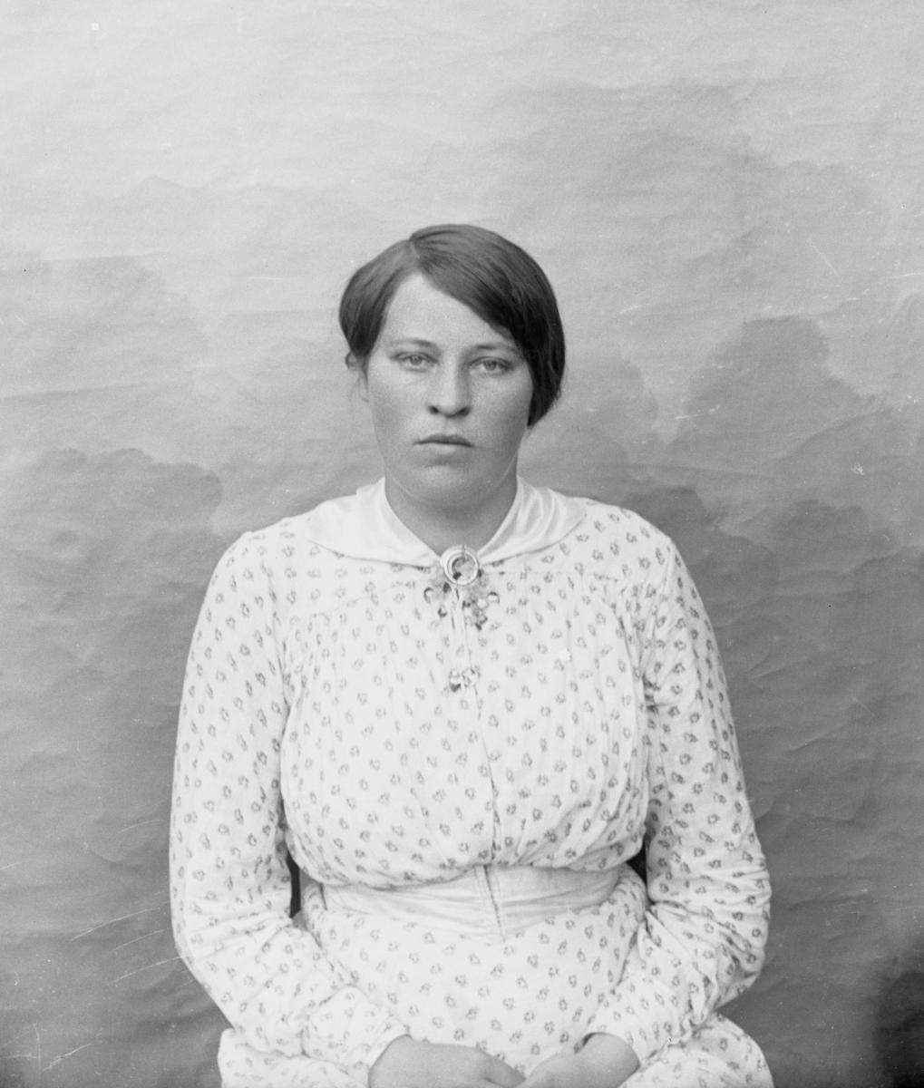 Kvinne kledd i hvit mønstrete kjole, sittende foran lerret