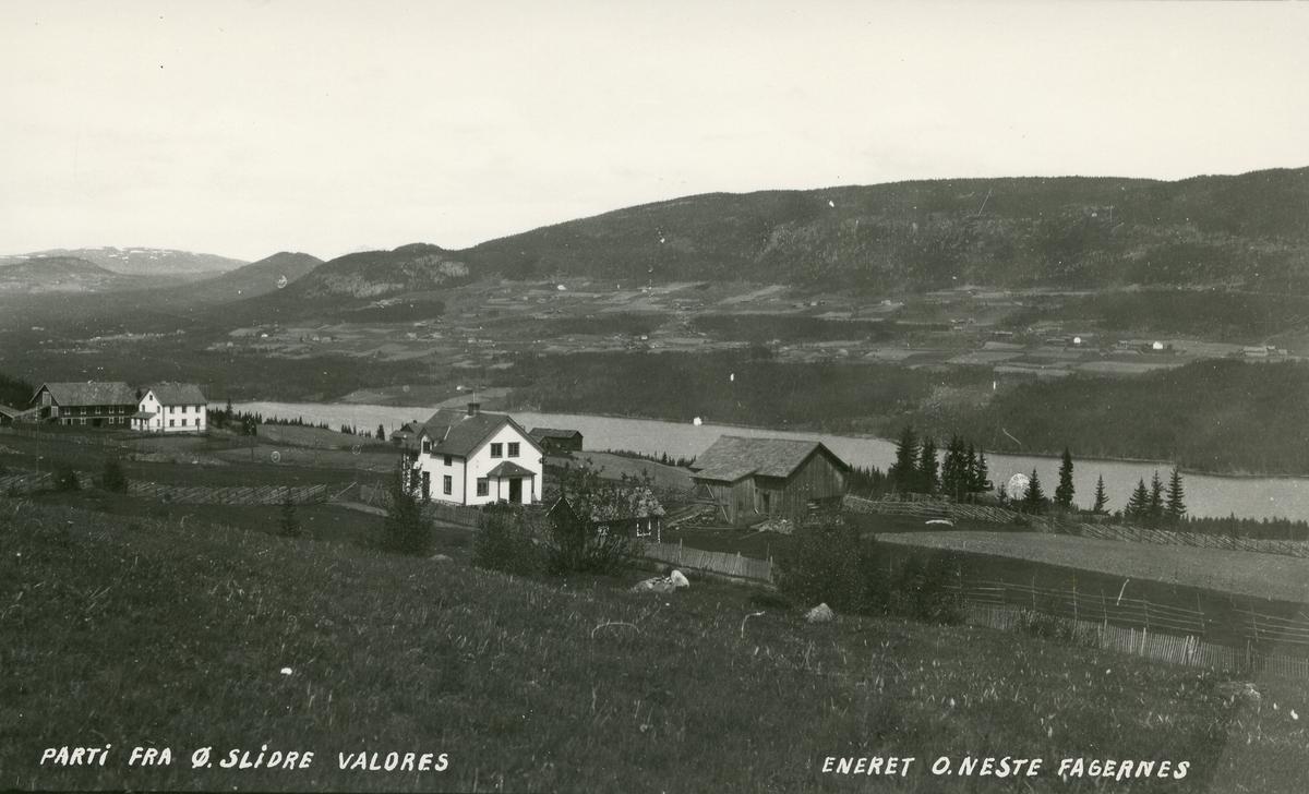 Utsikt fra vestsida i Øystre Slidre, mot Volbufjorden. Gården Dokken til venstre