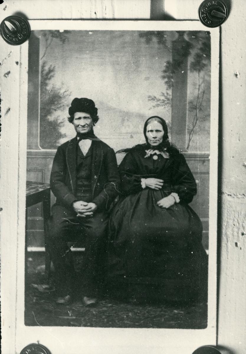 Fotografi festet på treplate med tegnestifter. Mann og kvinne, sittende, antagelig fra før 1900