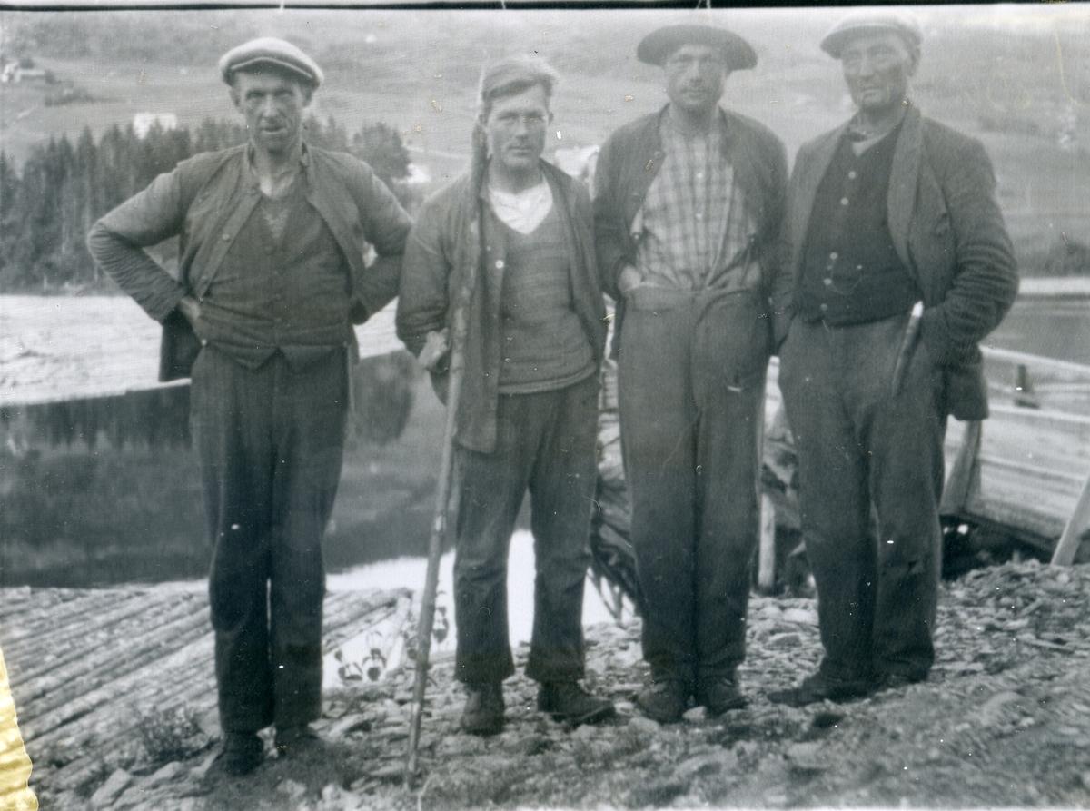Fire menn oppstilt i forbindelse med tømmerfløting, en holder en båtshake som ble brukt til å dra til seg og styre tømmeret med. Mann nr 2 fra høyre er muligens Jon Tuv fra Røn i Vestre Slidre