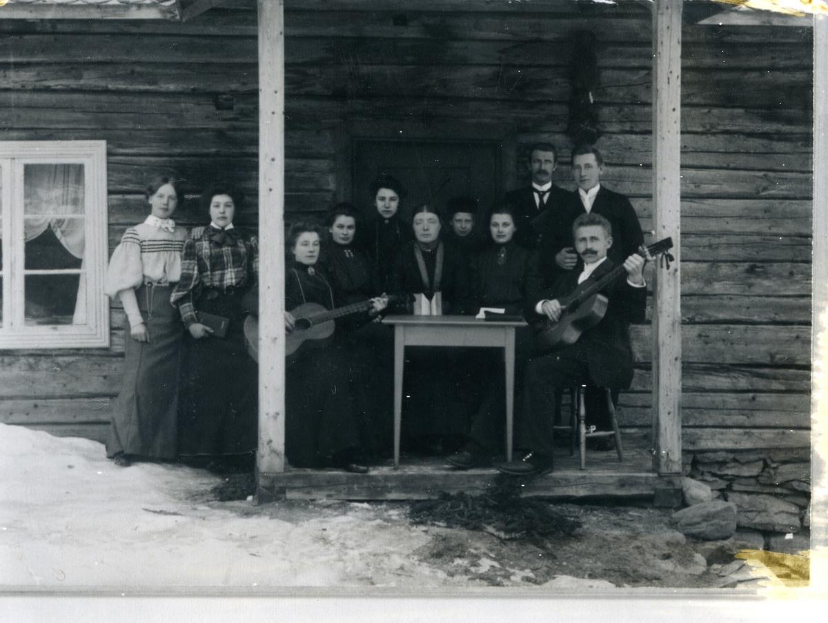Kvinner og menn oppstilt framfor inngang på tømmerbygning, to med gitarar. Mannen med gitar til høyre i bildet er emmisær Hans Evensen.