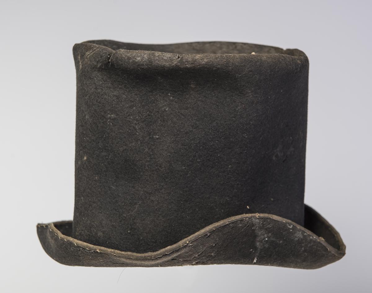 Filthatt med høy stiv pull som er flat på toppen.  Rundt ytterkanten av bremmen er det påsydd et smalt bånd.  2/3 av høyden av hatten er foret. Øvre del av hatten har større omkrets enn lenger nede. Denne type hatt er forløperen til flosshatt.