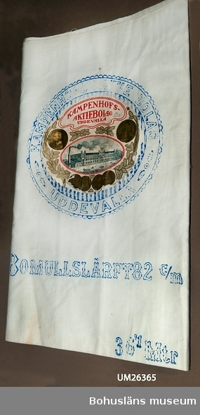 """Föremålet visas i basutställningen Uddevalla genom tiderna, Bohusläns museum, Uddevalla.  Vitt tygstycke. Blått tryck, text: """"KAMPENHOFS AKTIE BOLAG UDDEVALLA"""", i en cirkel. I cirkeln är det en pappersetikett med bl.a. fabriksbyggnaden avbildad samt eklöv och medaljer. Under cirkeln står det: """"BOMULLSLÄRFT 82 CM"""" samt 36""""1 Mtr"""". Givaren tror att tyget kommer från en affär i Lysekil."""