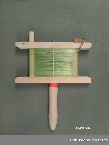 Träram av björk, vinda, fästad  mitt på ena långsidan i ett handtag så att den kan rotera. Handtaget fästat i ramen med en metallpinne. På ena långsidan är det en korkbit som man kan sätta fast kroken i då redskapet inte används.  En ljusgrön lina av polyamidfiber är upplindad på ramen med två stålkrokar och ett avlångt sänke av bly. Originalförpackning, plastpåse med pappförslutning märkt TRÄVINDA. På butikens den medföljande packsedel kallas redskapet vitlingmeta.  Inköpt till föremålssamlingarna i samband med utställningen Fri och ledig!? sommaren 2011. Text till utställningen Fri och Ledig!?: Sverige har fina möjligheter till fritidsfiske. 90 000 sjöar, 100 000 vattendrag och en lång kust. Det behöver inte vara dyrt. Men vi satsar gärna. Särskilt männen: 1,5 miljarder kronor läggs på båt och utrustning varje år. Fisketurism är en guldkantad nisch för näringslivet. Allt från hummersafari på Västkusten till exklusivt fiske i avlägsna fjällsjöar. Det finns en stor utländsk fisketurism. Utomlands är många vatten privatägda. Alla har rätt att fiska med handredskap vid kusten och i de fem stora sjöarna Vänern, Vättern, Mälaren, Hjälmaren och Storsjön. Man får meta, spinnfiska, pilka och pimpla och fiska med lina som har max 10 krokar. Till andra vatten kan man köpa fiskekort.