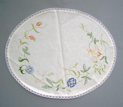 Duk MIA. Oval duk av blekt linnetyg med broderi i form av en slinga med blommor och blad längs kanten med en 15cm öppning på ena långsidan. Broderi i moulinégarn. Stjälk- och plattsöm i grönt, blått, gult och olika nyanser vitt/rosa/rött. Duken har en 10mm bred spets längs kanten.