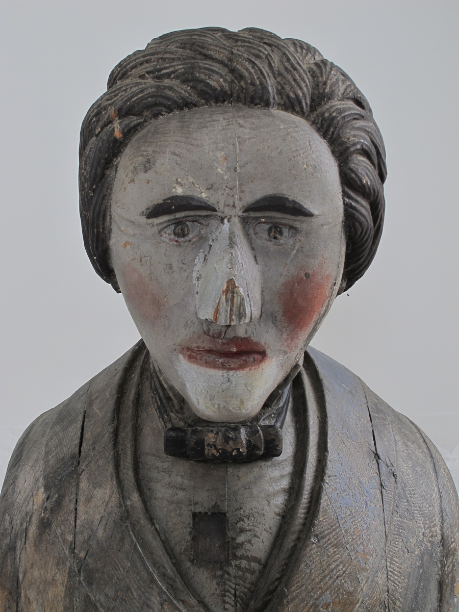 Byste av Henrik Wergeland.  hode med stor nese, tettsittende øyne, sorte buede bryn og stor gråsort manke, grå  (opprinnelig hvit) karnasjon med store røde flekker  i kinnene og rødmalt munn. Dobbeltknappet frakk, sort sløyfe.