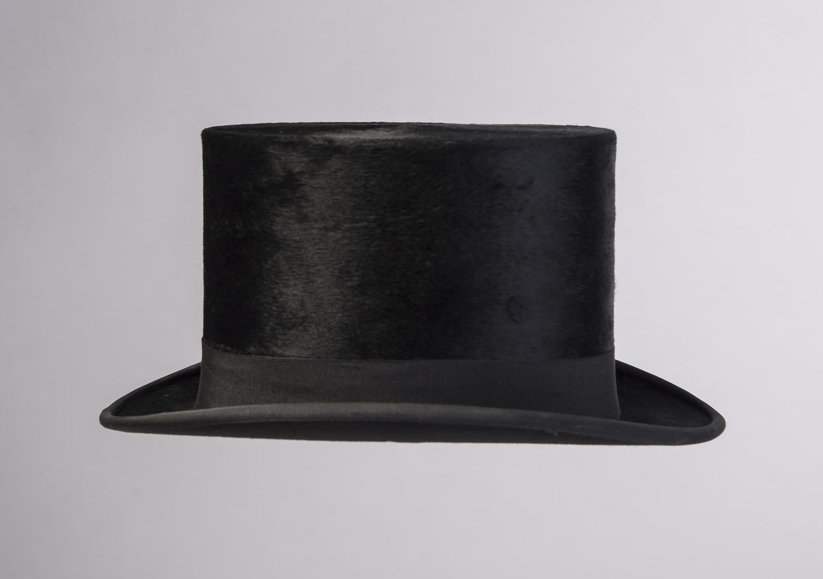 Flosshatt med høy stiv pull som er flat på toppen. Bremmen er flat fram og bak, oppbøyd ved sidene. Ytterkanten av bremmen har påsydd et ripsbånd. Undersiden av bremmen har et annet stoff enn resten av hatten. Rundt nedre del av pullen er det et ripsvevd dekorbånd. Hatten har bredt svettebånd  med sløyfe midt bak og hatten er fôret. Stempel inne i pullen.