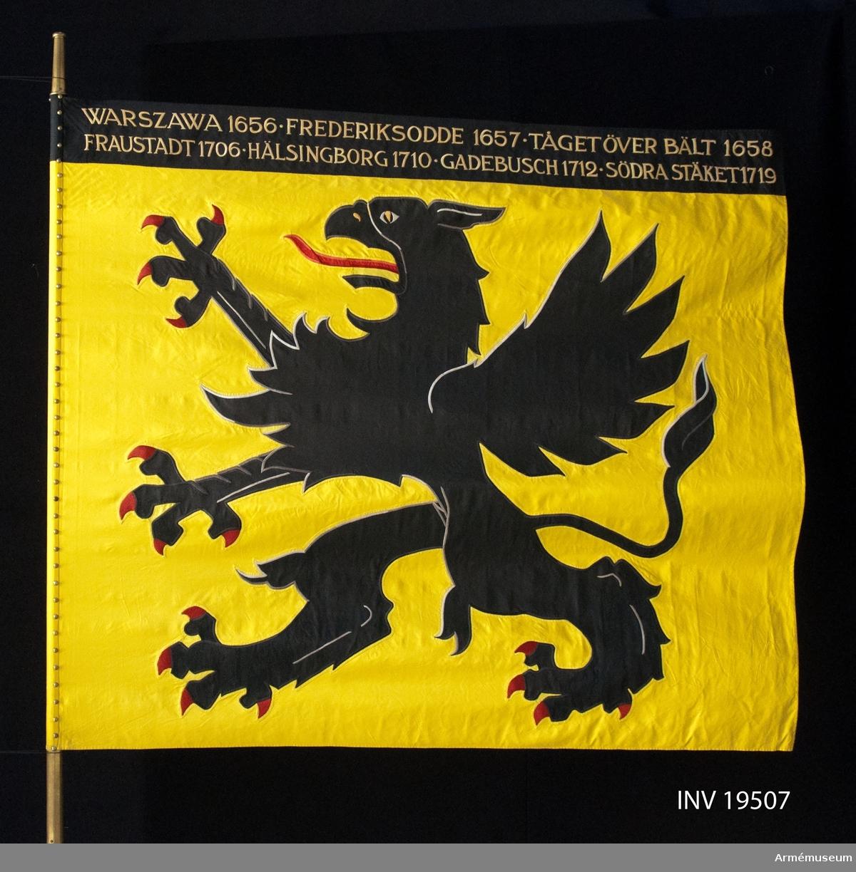 På gul duk landskapet Södermanlands vapenbild; en svart upprest grip med röd tunga. På svart bård i fanans överkant segergamn i gult. Duk av siden med dekor utförd i intarsia och handbroderi.