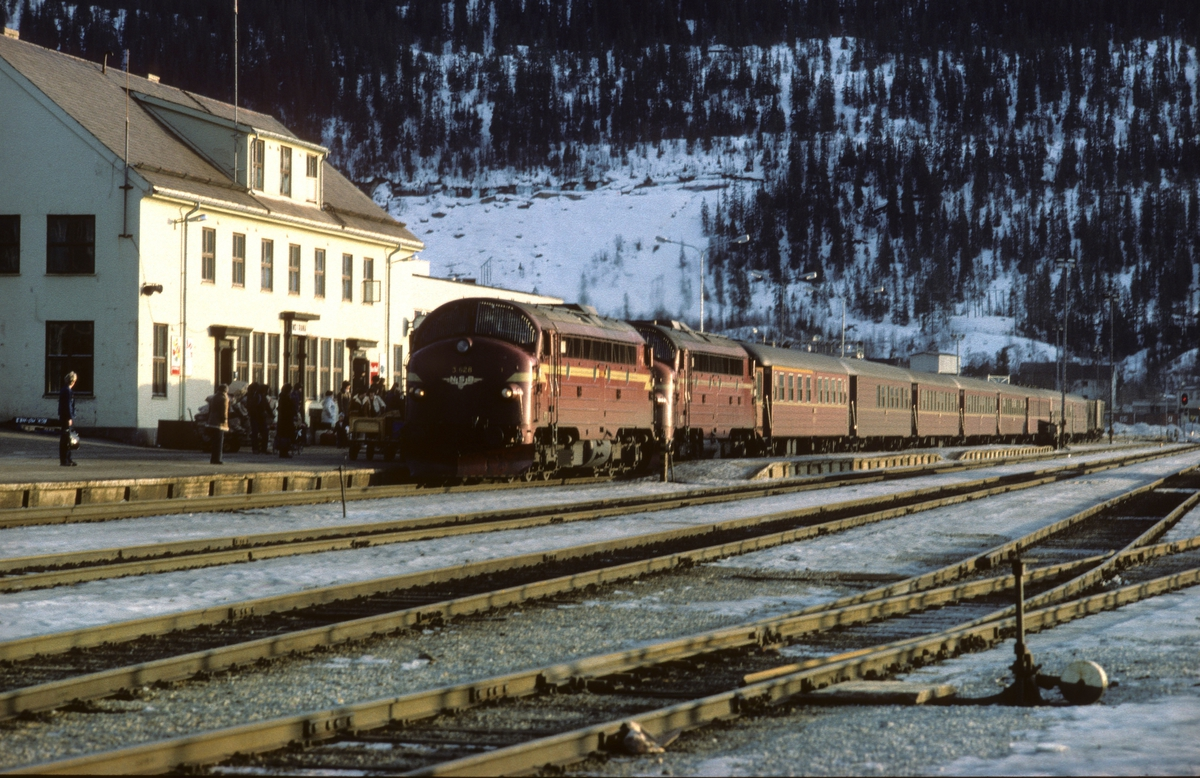 Dagtoget Trondheim - Bodø, tog 451, bremser inn på Mo i Rana stasjon. Toget trekkes av to diesellokomotiver type Di3 i fellesstyring med Di3 628 først. Vogner av type 3, og toget fører både 1. og 2. klasse samt kafeteriavogn.
