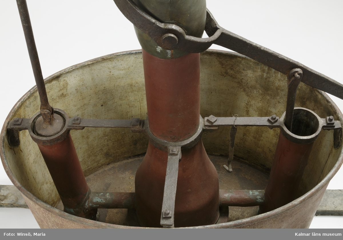 """KLM 45476. Brandspruta, metall, trä, läder, färg. Brandspruta med rödmålad vattenbehållare av plåt med oval form och två rundsvarvade handtag av trä. Inuti en pumpanordning, målad i grön och röd färg, med dubbla handtag för pumpning. Handtagen är diagonalt placerade på var sin sida av en tvärgående järnaxel. Det ena handtaget saknas, det kvarvarande är rödmålat. Högst upp på pumpanordningen ett hål och hylsa för anslutning av slang. I botten på vattenbehållaren ett avtappningshål och under två stöd av trä, varav det ena är avbrutet både fram och bak. På vattenbehållarens utsida målat """"Slottet"""". Tillhörande slang av läder med hylsa av mässing."""