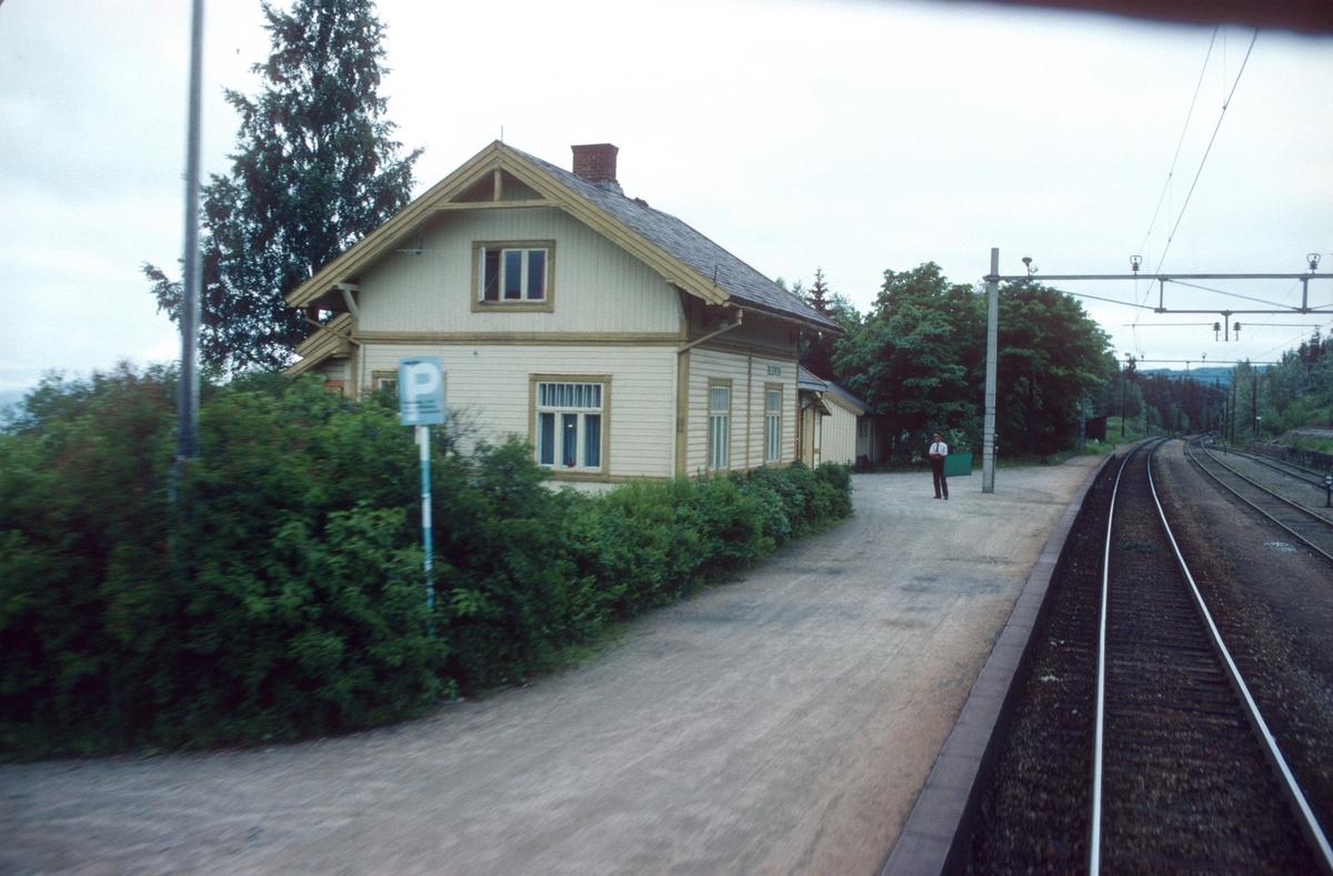 """Togekspeditøren på Bleiken stasjon viser signal """"Passer"""" (grønt flagg) til godstog 5173 (Roa - Eina)."""