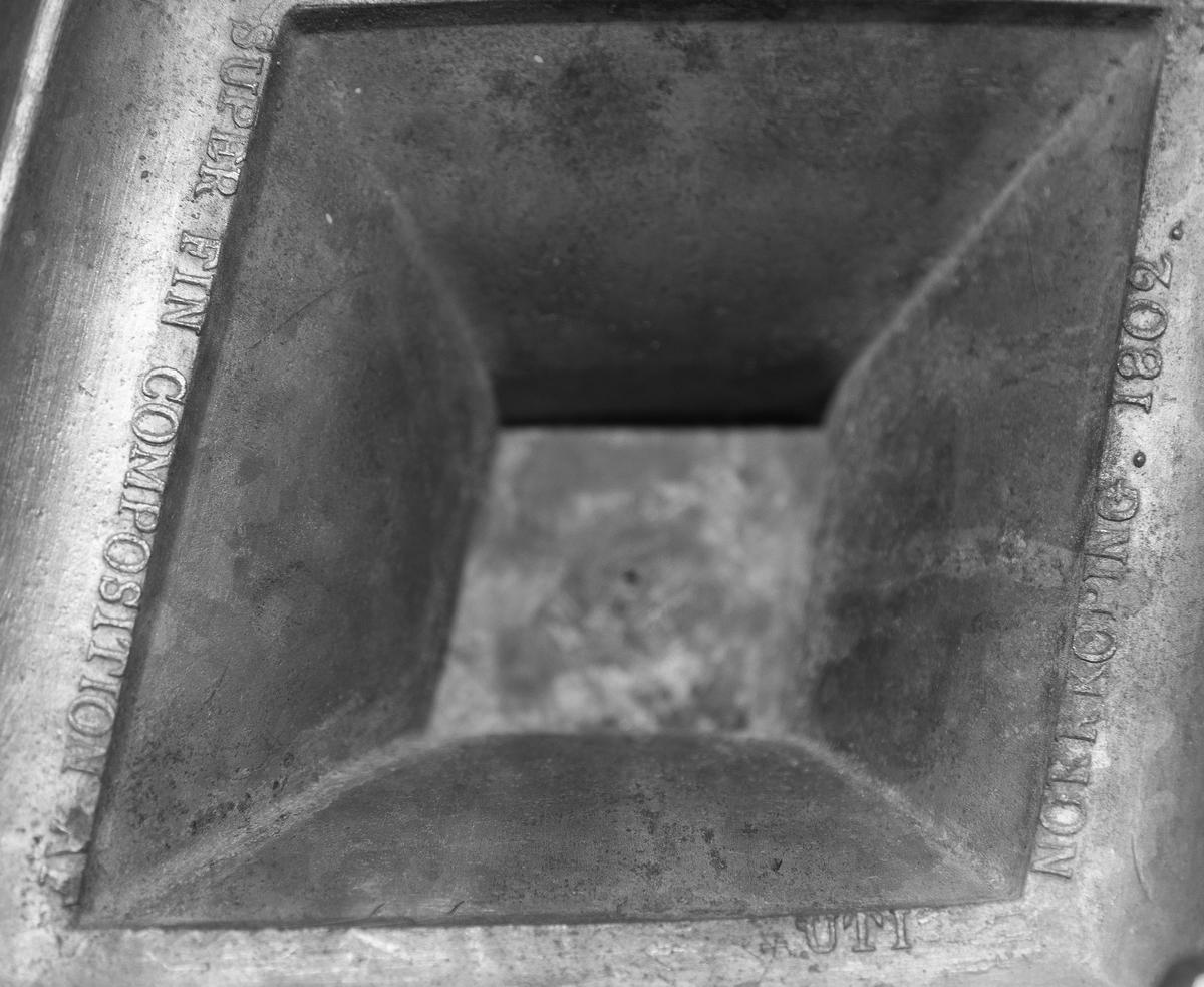 Ljusstake av tenn, möjligen engelskt tenn, britannica metall. Fyrsidigt, rombiskt slätt ben. Rombisk fot. Dekor runt fot och vid benets övre och nedre del. Ljusarm, går att ta av, med tre ljuspipor, en mitt på som träs på staken, en vardera i de S-formade armarnas avslutning. Droppskålar under samtliga ljuspipor.